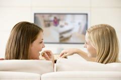 Twee vrouwen in woonkamer het letten op televisie Stock Foto
