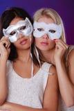Twee vrouwen zien met de Venetiaanse maskers van Carnaval onder ogen Stock Afbeeldingen