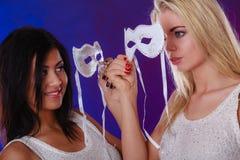 Twee vrouwen zien met de Venetiaanse maskers van Carnaval onder ogen Stock Afbeelding