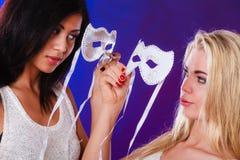 Twee vrouwen zien met de Venetiaanse maskers van Carnaval onder ogen Stock Fotografie