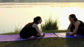 Twee vrouwen zitten op matten, buigen vooruit en houden voeten bij zonsondergang samen stock video
