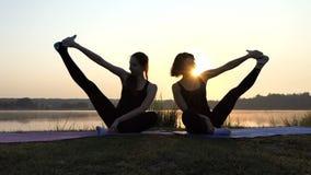 Twee Vrouwen zitten op Matten, opheffen Benen opzij, Glimlach, bij een Schitterende Zonsondergang stock videobeelden