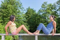 Twee vrouwen zitten tegenovergesteld op brugtraliewerk stock afbeeldingen