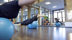Twee vrouwen zwarte sportswear do exercises op fitball in gymnastiek stock video