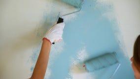 Twee vrouwenarbeiders die rol met behulp van om de muren in de flat of het huis te schilderen Bouw, reparatie en vernieuwing stock video