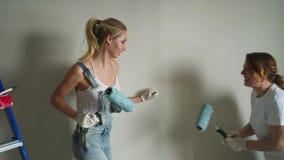 Twee vrouwenarbeiders die rol met behulp van om de muren in de flat of het huis te schilderen Bouw, reparatie en vernieuwing stock videobeelden