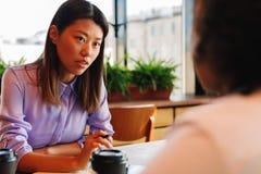Twee vrouwenbespreking in een koffie Stock Foto