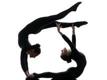 Twee vrouwencontorsionist die gymnastiek- yogasilhouet uitoefenen Stock Foto