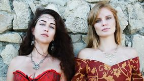 Twee vrouwengezichten die aan vestingsmuur achteruitgaan stock video
