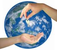 Twee vrouwenhanden die sleutel van de geïsoleerdes aarde geven Stock Afbeeldingen
