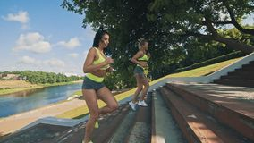 Twee vrouwenjogging op treden Paar die van agent treden in sportslijtage beklimmen stock videobeelden