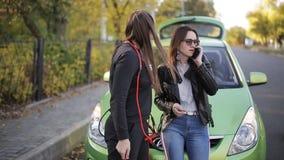 Twee vrouwenmeisje die cellphone roepen dichtbij haar gebroken auto Twee vrouwen die zich dichtbij gebroken auto op de weg bevind stock video