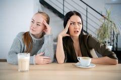 Twee vrouwenvriend die bij elkaar, slecht verhoudingsconcept mokken stock afbeeldingen