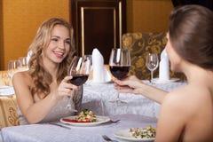 Twee vrouwenvrienden die bij restaurant en het spreken eten Royalty-vrije Stock Afbeeldingen