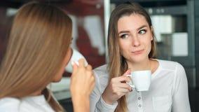 Twee vrouwenvrienden in een keuken het drinken koffie, het spreken van en het hebben van pret stock footage