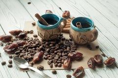 Twee weinig oude aardewerk met de hand gemaakte koppen koffie, koffiebonen, zoete droge data en pijpjes kaneel Stock Afbeelding