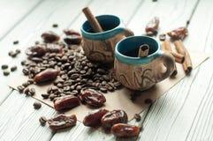 Twee weinig oude aardewerk met de hand gemaakte koppen koffie, koffiebonen, zoete droge data en pijpjes kaneel Royalty-vrije Stock Fotografie
