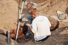 Twee werk in uitvoering in openlucht, in graafproces Archeologische uitgravingen stock afbeeldingen