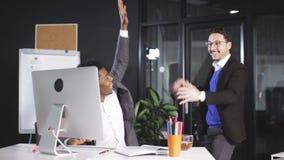 Twee werknemers die handen opheffen wanneer met succes het sluiten van grote transactie stock video