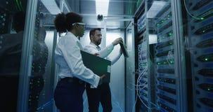 Twee werknemers die onderhoud in een datacentrum uitvoeren stock video