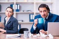 Twee werknemers die op het werk lijden stock foto