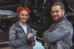 Twee werktuigkundigen die een auto herstellen stock afbeeldingen