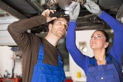 Twee werktuigkundigen die een auto in hydraulische lift herstellen Royalty-vrije Stock Fotografie