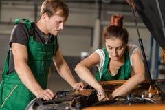 Twee werktuigkundigen herstellen de motor van een oranje auto royalty-vrije stock fotografie