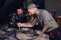 Twee werktuigkundigen het bevestigen auto` s motor in een garage royalty-vrije stock afbeeldingen
