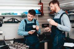 Twee Werktuigkundigen op Benzinestation Koffie het drinken stock foto