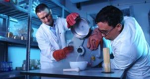 Twee wetenschappers die chemisch product in mortier 4k gieten stock footage