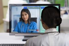 Twee wijfjes arts die teleconferentietechnologie gebruiken aan discutsion over geduldig geval stock afbeeldingen
