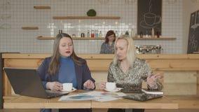 Twee wijfjes die koffie drinken die bij koffielijst werken stock footage