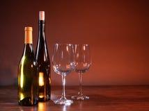 Twee wijnflessen en twee wijnglazen op een eenvoudige achtergrond stock afbeeldingen