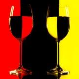 Twee wijnglazen in backlight op het rood en yello Royalty-vrije Stock Foto's