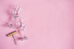 Twee wijnglazen en een kurketrekker op een roze achtergrond Stock Afbeeldingen
