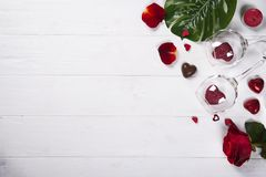 Twee wijnglazen met rode harten, namen bloemblaadjes en chocoladesnoepjes toe Stock Foto's