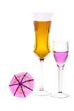 Twee wijnglazen worden gevuld met gekleurde dranken Stock Afbeelding