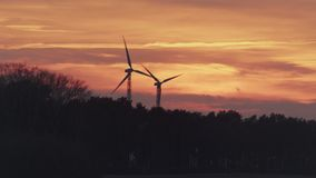 Twee Windturbines achter Donker Forest At Sunset stock video