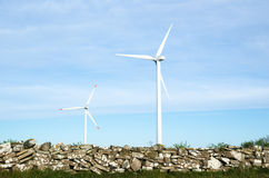 Twee windturbines door oude traditioneel obstructie voeren in het Zweeds Stock Afbeeldingen