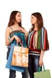 Twee winkelende meisjes die op wit worden geïsoleerdg Stock Foto's