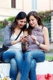 Twee winkelende meisjes in park met een mobiele telefoon Stock Foto