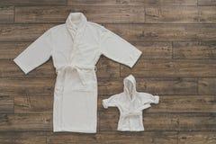Twee witte badjassen op houten achtergrond Stock Fotografie