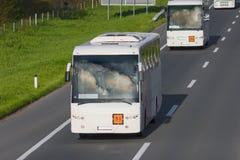 Twee witte bussen op de weg bij zonnige dag royalty-vrije stock foto's