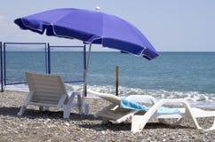 Twee witte chaise zitkamerstribunes op zeekust Royalty-vrije Stock Foto's