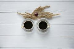 Twee witte en gouden koppen van koffie met decoratieve gouden takken en klein glas en rode hart op witte houten achtergrond Royalty-vrije Stock Afbeelding