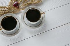 Twee witte en gouden koppen van koffie met decoratieve gouden takken en klein glas en rode hart op witte houten achtergrond Royalty-vrije Stock Foto