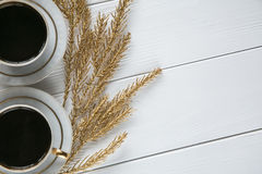 Twee witte en gouden koppen van koffie met decoratieve gouden takken en klein glas op witte houten achtergrond Royalty-vrije Stock Foto's