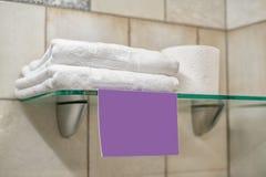 Twee witte handdoeken, een broodje van toiletpapier en een leeg lilac etiket Royalty-vrije Stock Afbeeldingen