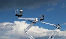 Twee witte kersenplukkers tegen blauwe hemel met wolken, onder zijn er pluizige wolken, boven donkere wolken Royalty-vrije Stock Afbeelding